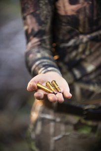 USA, Texas, Young woman holding Caliber 30-30 cartridgesの写真素材 [FYI04333534]