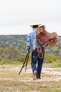 Texas, Cowboy walking with rifle and saddleの写真素材 [FYI04333538]