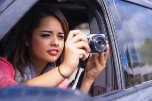 Teenage girl taking picture out of carの写真素材 [FYI04333550]