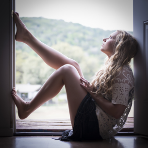 Portrait of young woman sitting on window sill looking aboveの写真素材 [FYI04333570]