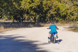 USA, Texas, Little boy riding bike with stabilisersの写真素材 [FYI04333572]