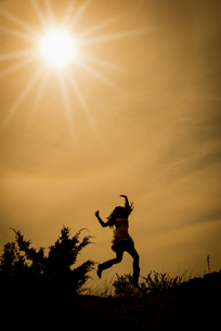 Silhouette of jumping woman in backlightの写真素材 [FYI04333578]