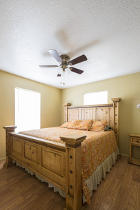 USA, Texas, Rustic Bedroom Interior with Ceiling Fanの写真素材 [FYI04333593]