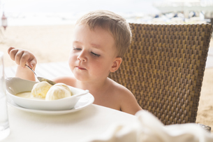 Mexico, portrait of toddler sitting at a table eating ice crの写真素材 [FYI04333618]