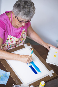 Senior woman painting an abstract pictureの写真素材 [FYI04333625]
