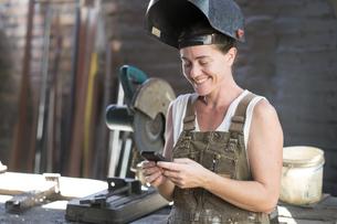 Female welder in metal workshop using mobile phoneの写真素材 [FYI04333630]