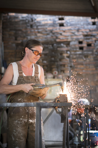 Female welder working in metal workshopの写真素材 [FYI04333633]