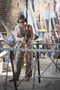 Female welder working in metal workshopの写真素材 [FYI04333634]