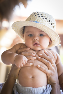 Portrait of baby boy with straw hat being heldの写真素材 [FYI04333641]