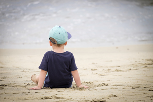 Back view of little boy sitting on the beach at seafrontの写真素材 [FYI04333649]