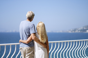 Senior couple looking at view on balcony by the seaの写真素材 [FYI04333657]