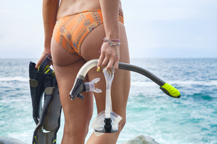 Young woman with diving equipment by the seaの写真素材 [FYI04333658]