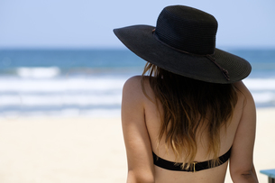 Back view of female teenager with hat at the beachの写真素材 [FYI04333660]