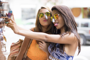 Two young women trying sunglasses on and taking a selfieの写真素材 [FYI04333663]