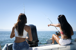 Two young women fishing on a boat tripの写真素材 [FYI04333668]