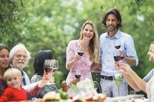 Couple holding glasses of red wine on a garden partyの写真素材 [FYI04333671]