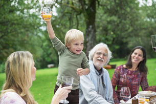 Boy holding glass on a garden partyの写真素材 [FYI04333673]