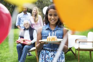 Girl in garden holding birthday cakeの写真素材 [FYI04333677]