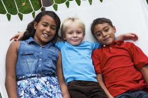 Three children lying in hammockの写真素材 [FYI04333678]