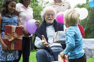 Grandfather receiving gifts on birthday party in gardenの写真素材 [FYI04333686]