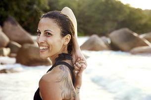 Seychelles, portrait of smiling woman with tatoo doing yogaの写真素材 [FYI04333688]