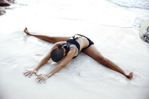 Seychelles, woman doing yoga exercise at seafrontの写真素材 [FYI04333689]