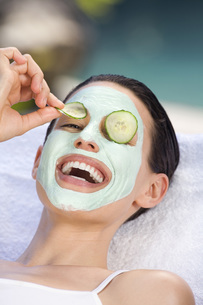 Young woman with face mask and cucumber slices, portraitの写真素材 [FYI04333703]