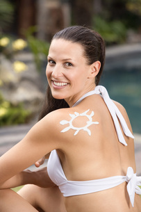 Woman with sun cream in shape of sun on shoulderの写真素材 [FYI04333705]