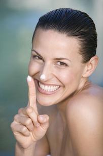 Young woman applying facial cream, portraitの写真素材 [FYI04333708]