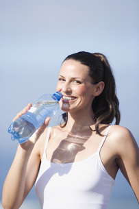 Young woman drinking water, portraitの写真素材 [FYI04333710]