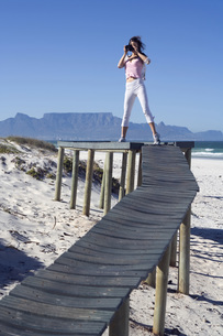 South Africa, Cape Town, Young woman taking photograph, portの写真素材 [FYI04333711]