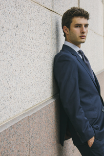 Portrait of young businessman leaning against wallの写真素材 [FYI04333722]