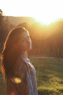 Portrait of woman in a park at backlightの写真素材 [FYI04333723]