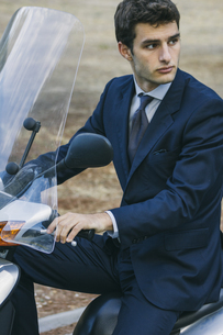 Portrait of young businessman sitting on motor scooterの写真素材 [FYI04333724]