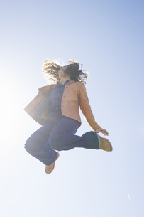Young woman jumping in the air at backlightの写真素材 [FYI04333726]