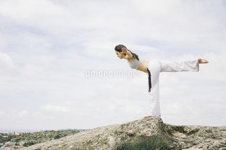 Woman doing yoga exercises on a mountainの写真素材 [FYI04333728]