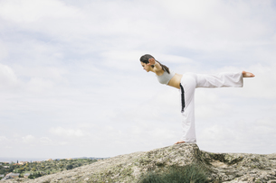 Woman doing yoga exercises on a mountainの写真素材 [FYI04333728]