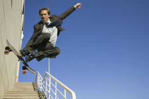 Businessman jumping with his skateboardの写真素材 [FYI04333731]