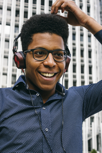 Smiling young man with headphones outdoorsの写真素材 [FYI04333732]