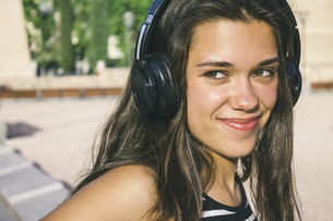Portrait of smiling teenage girl listening music with headphの写真素材 [FYI04333733]