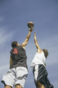 Young men playing basketball, jumping mid-airの写真素材 [FYI04333737]