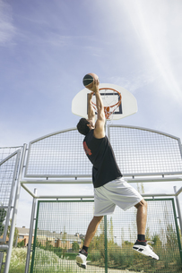 Young man playing basketball, dunking ballの写真素材 [FYI04333739]