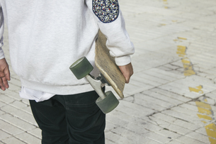 Young man carrying his longboardの写真素材 [FYI04333740]