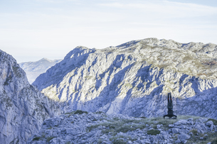 Spain, Asturias, Man doing a handstand with mountain landscaの写真素材 [FYI04333744]