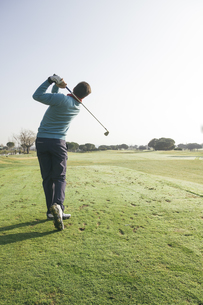 Golfer hitting a golf ball on a golf courseの写真素材 [FYI04333748]