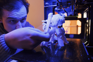 Man examining a figure of a robot printed by a 3D printerの写真素材 [FYI04333751]