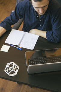 Business man using a laptop in a 3D printer officeの写真素材 [FYI04333753]