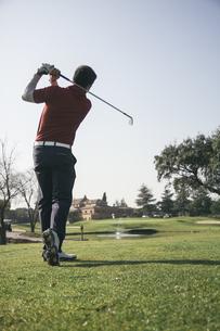 Golfer hitting a ball on a golf courseの写真素材 [FYI04333755]