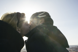 Young couple kissing at backlightの写真素材 [FYI04333759]