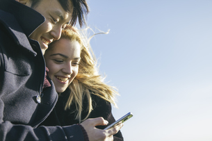 Young couple looking at smartphoneの写真素材 [FYI04333761]
